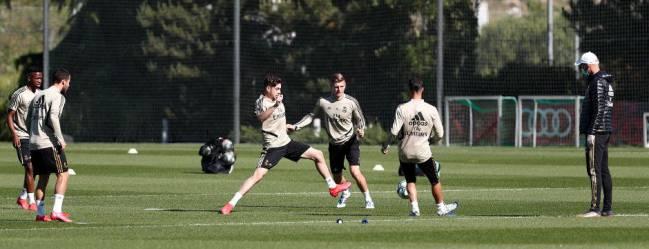 Zidane, siguiendo un ejercicio de posesión de sus jugadores este martes en Valdebebas.