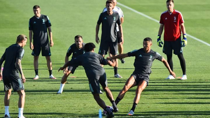 Cristiano y Cuadrado pugnan por un balón durante el entrenamiento de la Juventus, ayer.
