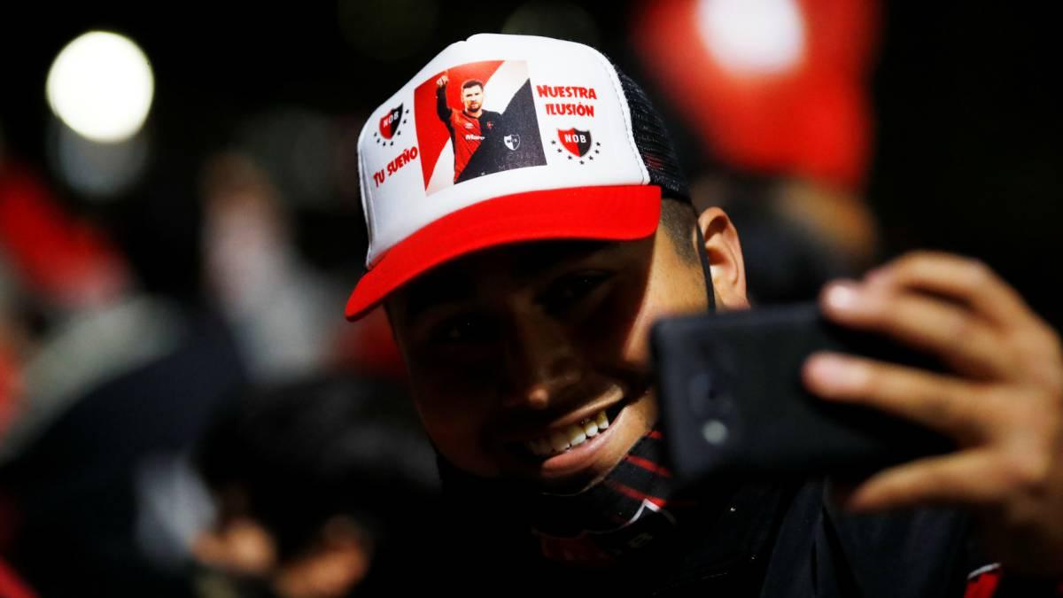 """Un hincha rosarino se hace un selfie con una gorra con la imagen del crack y el slogan """"Tu sueño, nuestra ilusión""""."""