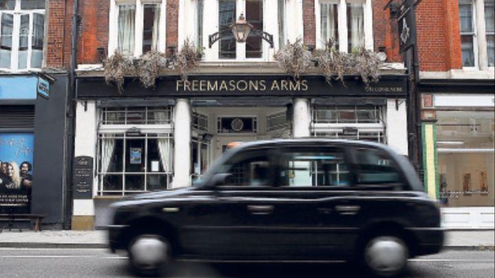 Un taxi londinense pasa por delante del histórico Freemasons Arms.