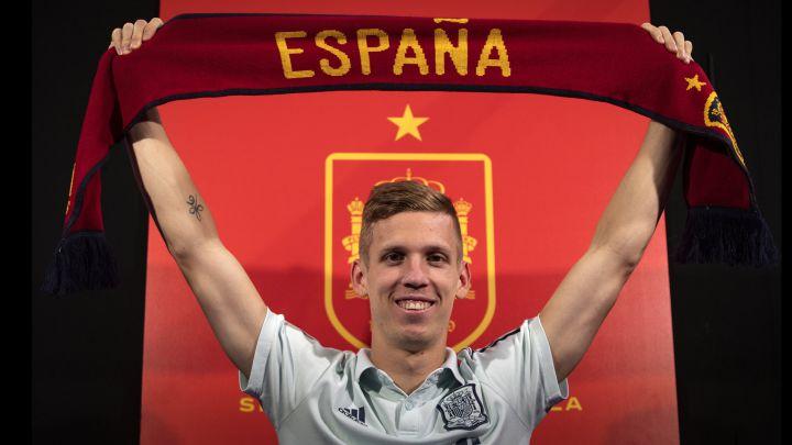 Dani Olmo posa con una bufanda de España delante del escudo de la Federación.