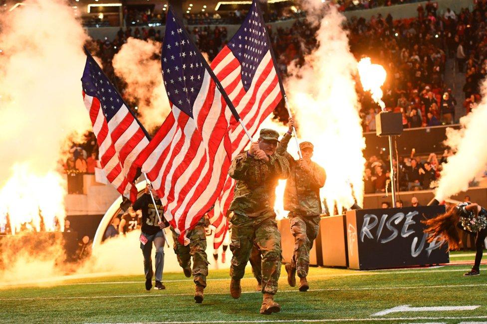 Miembros del cuerpo militar de Estados Unidos salen al campo antes del comienzo del partido entre los New York Giants y los Atlanta Falcons.