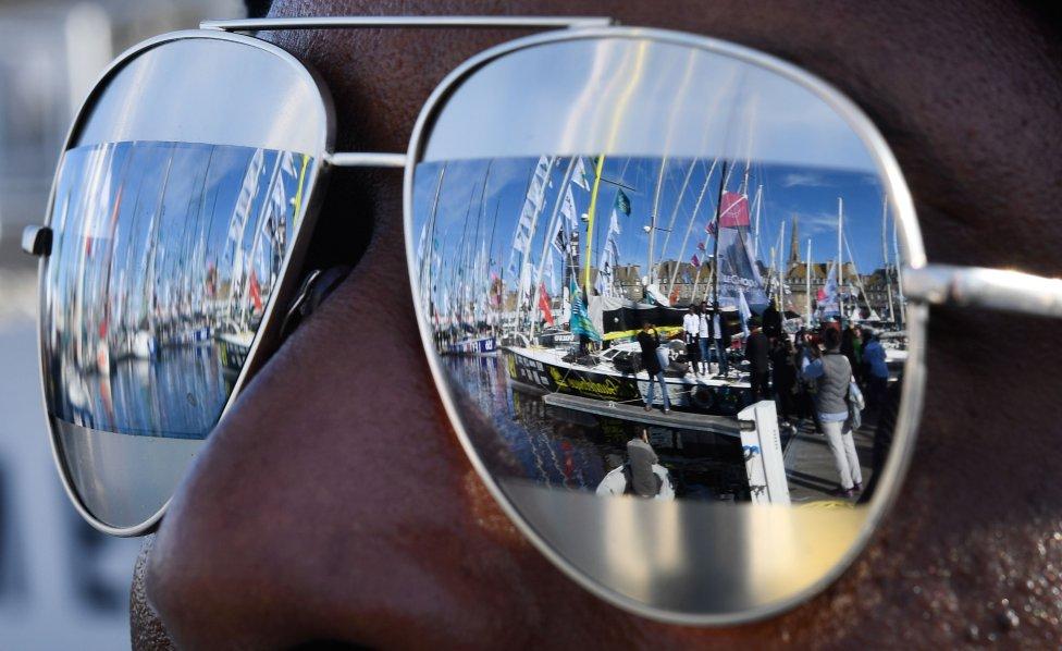 Unos barcos se reflejan en los cristales de las gafas de sol de una aficionada durante la Route du Rhum (creada en 1978). Es una carrera en solitario que se celebra cada cuatro años entre Saint-Malo y Pointe-a-Pitre, en las Antillas francesas, este año celebra su 40 aniversario.
