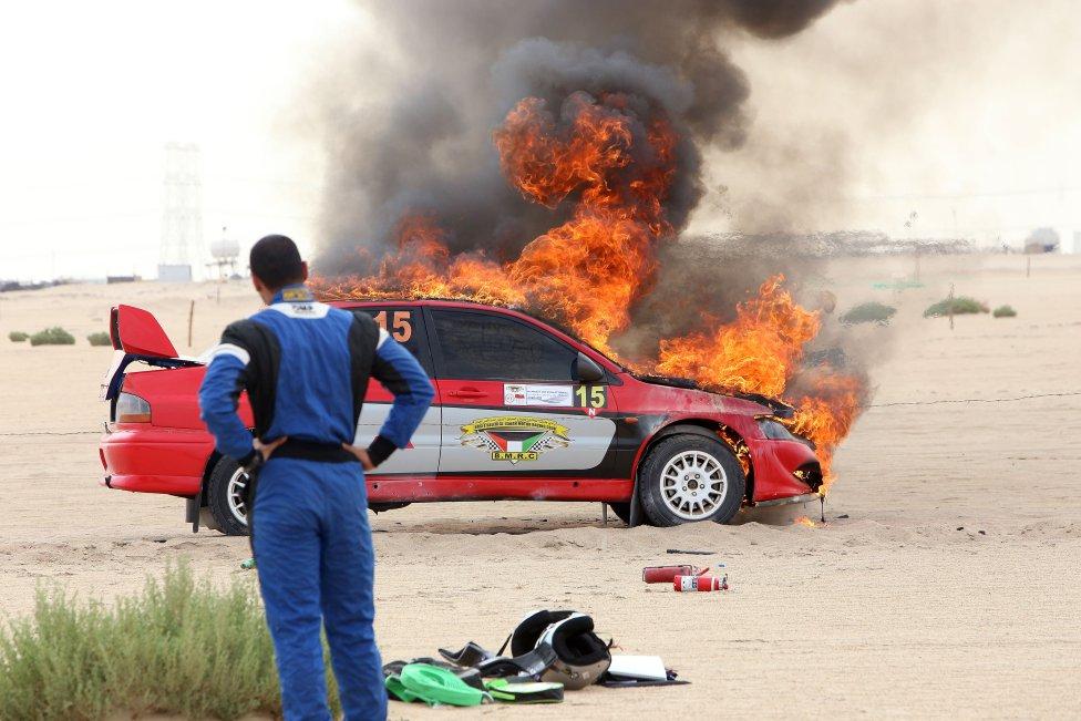 El copiloto kuwaití, Faris, mira arder su Mitsubishi Lancer Evolution VIII durante el Rally Internacional de Kuwait.