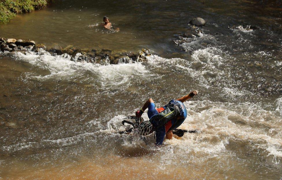El costarricense Juan Gabriel Valerin Machado cruza un río con su bicicleta durante el Día 1 de La Ruta de los Conquistadores en Jacó, Costa Rica. La Ruta de los Conquistadores es la principal carrera de ciclismo de montaña de Costa Rica y una de las más difíciles del mundo. Es una carrera por etapas de 3 días que atraviesa Costa Rica desde la costa del Pacífico en el oeste hasta la costa del Caribe en el este. Entre el inicio y el final a nivel del mar, la ruta de 161 millas cruza 5 cadenas montañosas.