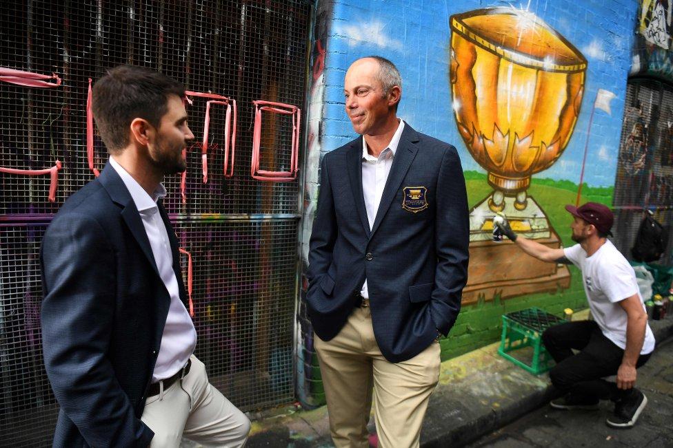 Matt Kuchar y Kyle Stanley del equipo estadounidense charlan durante la presentación de la Copa Mundial de Golf en Melbourne mientras un grafitero dibuja en la pared.