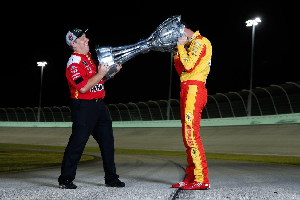 El piloto Joey Logano del equipo Shell Pennzoil Ford, y el jefe de equipo Tony Gibson posan para una foto tras ganar la Ford Cup de la Copa NASCAR de Monster Energy Ford EcoBoost 400 y el Campeonato de la Copa NASCAR de Monster Energy en Homestead-Miami Speedway.