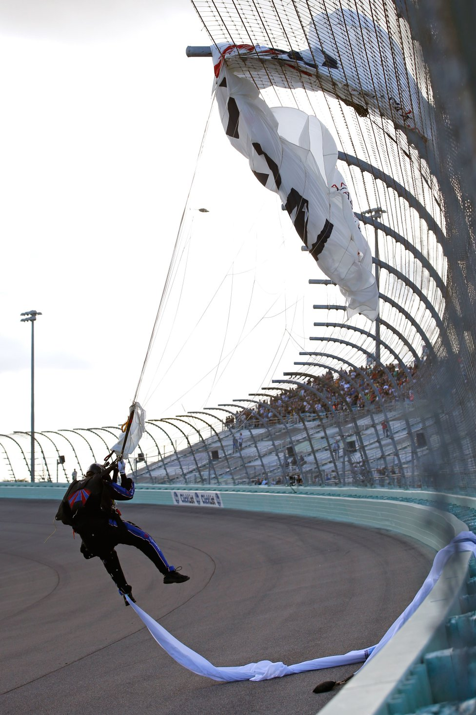 Un paracaidista se queda atrapado en la valla durante las ceremonias previas a la carrera de la serie NASCAR Cup Ford EcoBoost 400 de Monster Energy en Homestead-Miami Speedway.