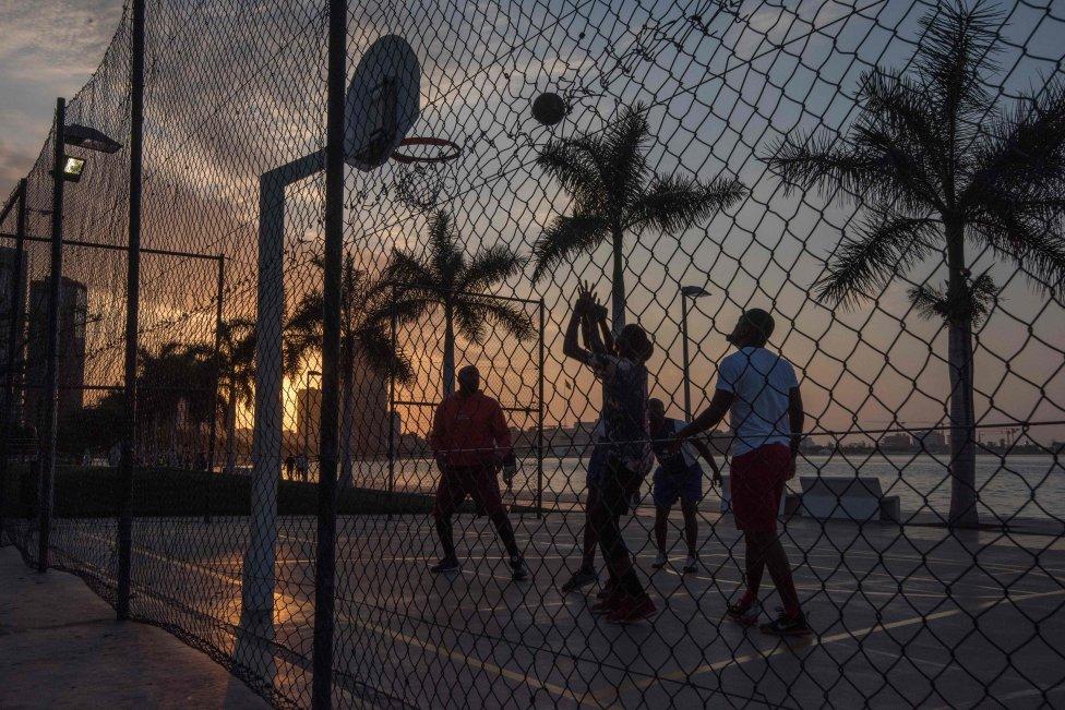 Tarde de Baloncesto en el Marginal, la pasarela construida en el borde de la bahía en Luanda. El mar es fundamental para la gente de Luanda para relajarse en la playa