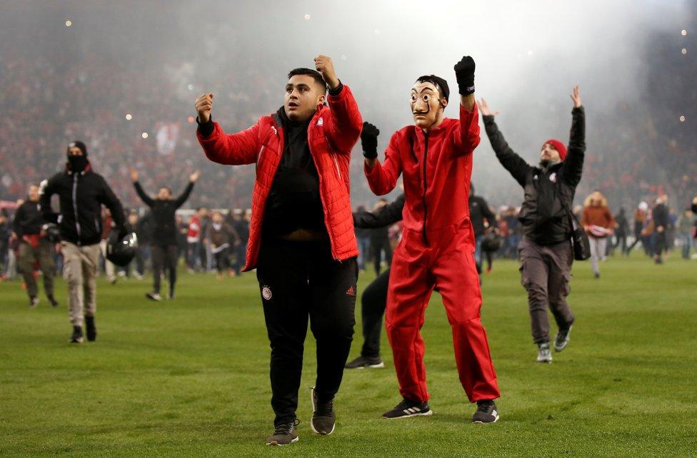 Los fanáticos del Olympiacos invaden el campo después del partido contra el AC Milan