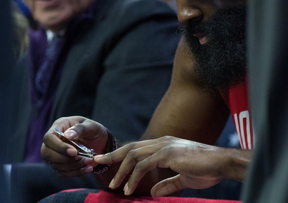 El jugador de los Houston Rockets James Harden se corta las uñas en el banquillo.