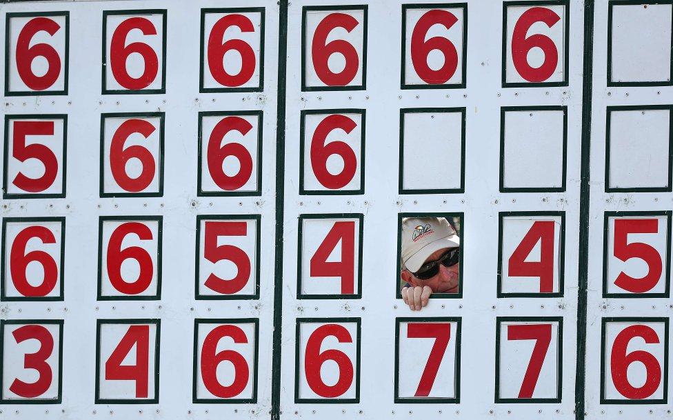 El encargado del marcador observa el partido de golf a través de un agujero numérico durante la segunda ronda del Arnold Palmer Invitational en el Bay Hill Club en Orlando, Florida.