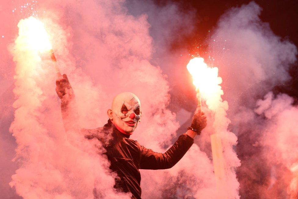 Un aficionado del St. Pauli disfrazado de payaso y con dos bengalas durante el encuentro de su equipo frente al Hamburgo SV.