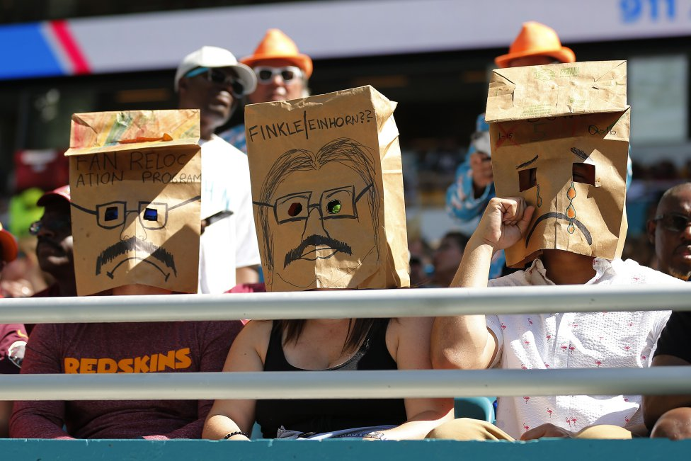 Tres aficionados durante el partido entre Miami Dolphins y the Washington Redskins.