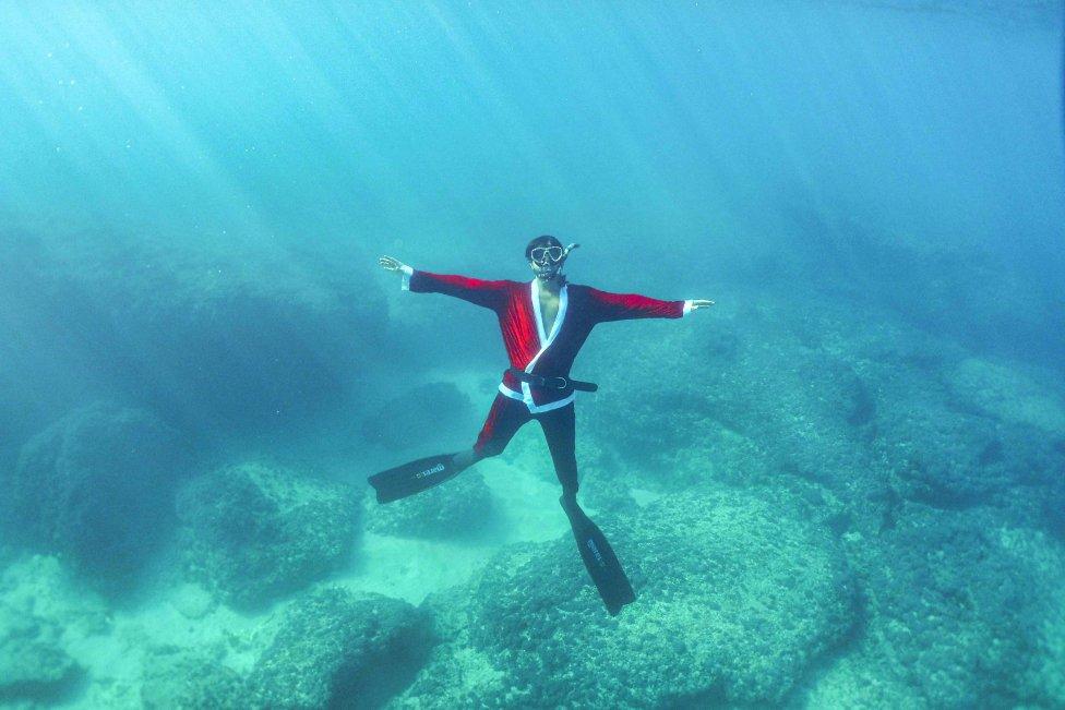 Un apneísta libanés disfrazado de Papá Noel posa bajo el agua frente a la costa de la ciudad norteña de Batroun.