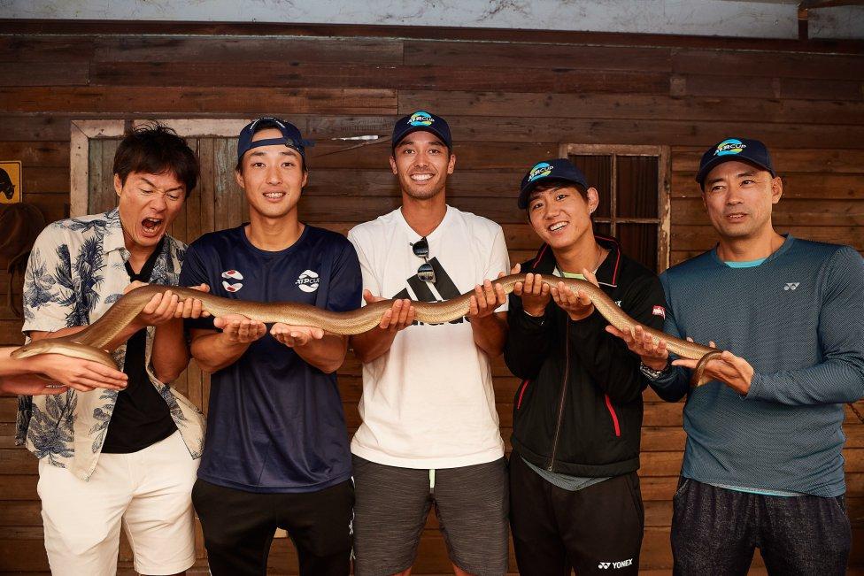 Los integrantes del equipo japonés de tenis para la ATP Cup, Go Soeda, Toshihide Matsui, Ben McLachlan, Yoshihito Nishioka y Satoshi Yabushi posan con una serpiente en el Caversham Wildlife Park en Australia.