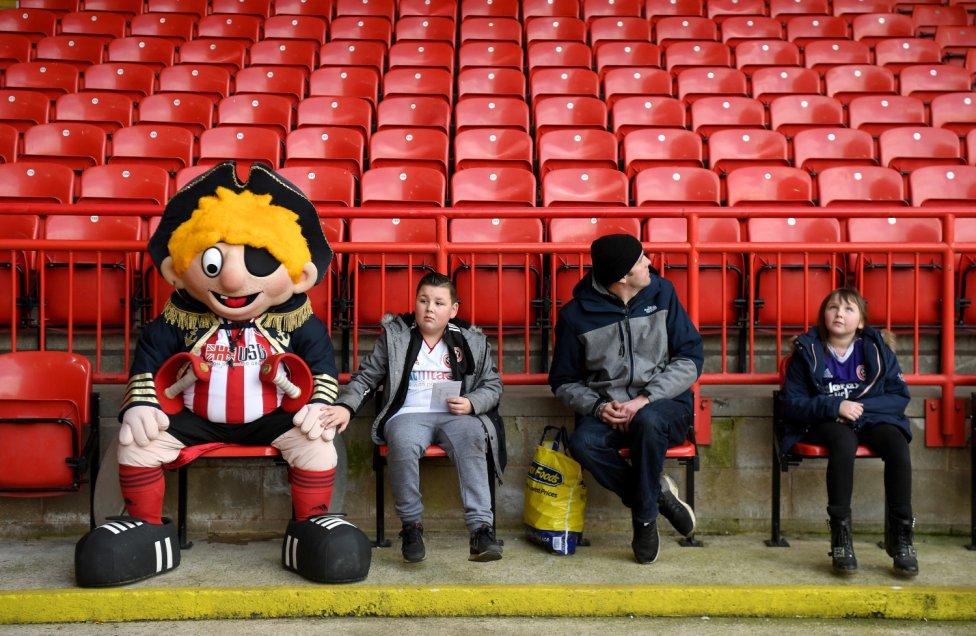 Tierna estampa de unos seguidores del Sheffield United y su mascota.