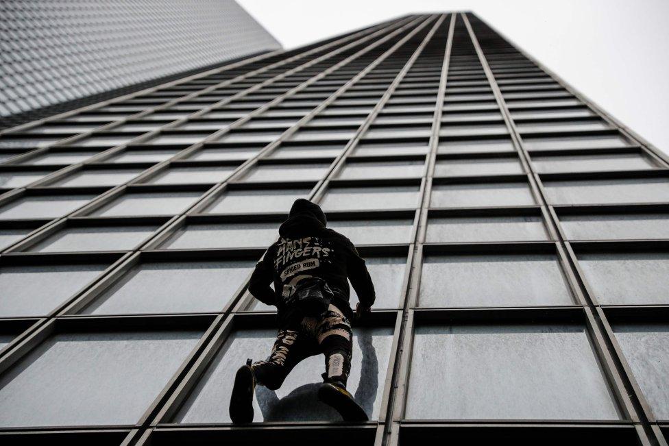 """El escalador de rascacielos francés Alain Robert, conocido popularmente como el """"Spiderman francés"""", comienza la escalada de la torre Total en el oeste del distrito comercial de La Defense de París, como una acción simbólica para apoyar a los trabajadores en huelga del movimiento nacional contra la reforma de las pensiones propuesta por el gobierno francés."""