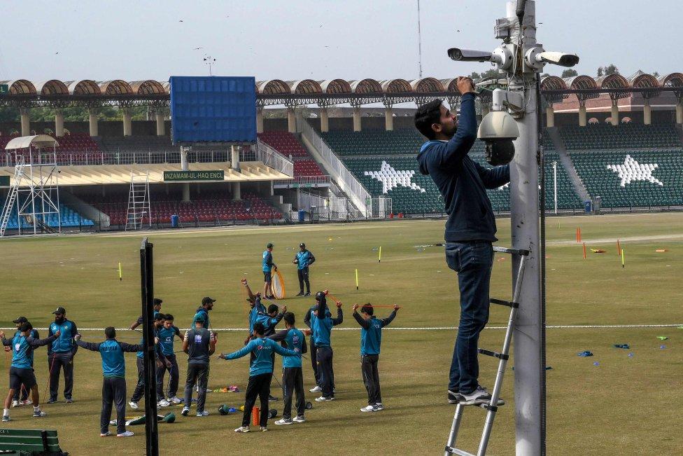 Un técnico coloca las cámaras de seguridad mientras los jugadores de críquet de Pakistán entrenan en el Estadio de Gaddafi en Lahore.