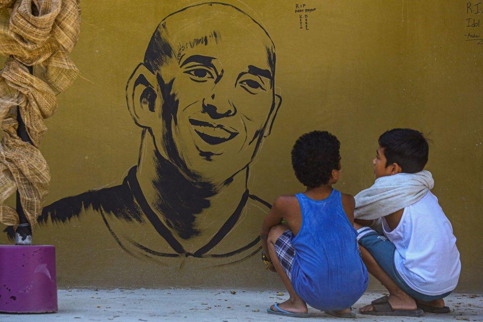 """Dos niños observan el muro conmemorativo del ex jugador de baloncesto de los Lakers, Kobe Bryant, tras su muerte. El mural se encuentra cerca del gimnasio """"House of Kobe"""" construido en honor a su visita de 2016 en Manila, Filipinas."""