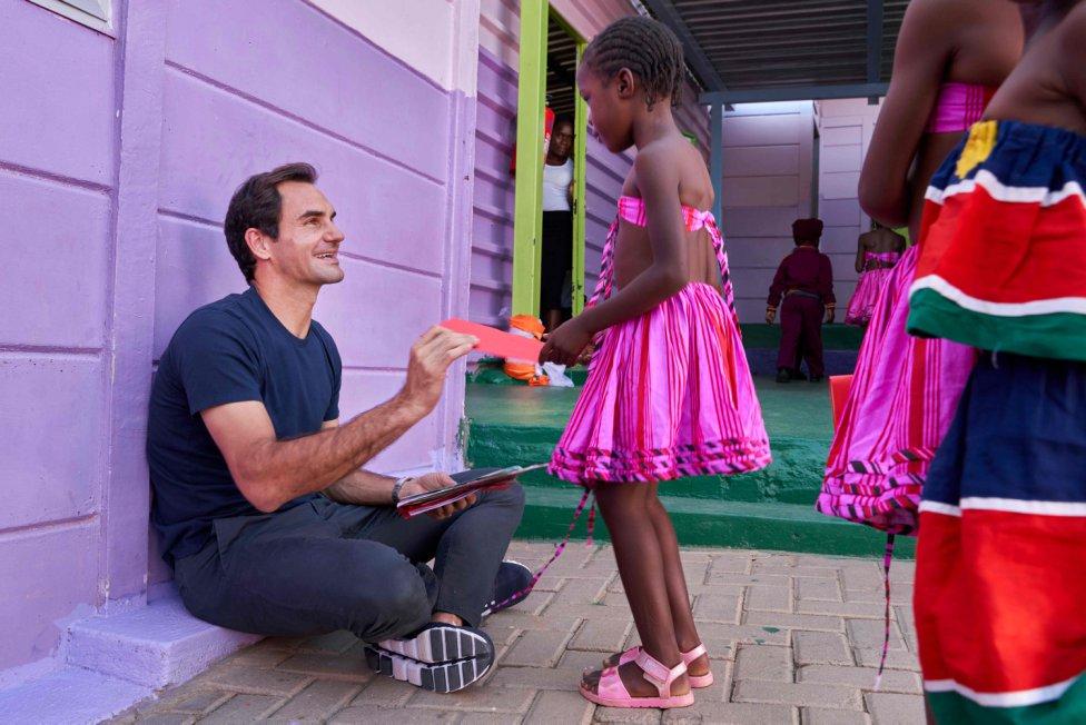 El tenista suizo Roger Federer compartiendo una sonrisa con una joven de la Fundación Roger Federer en Windhoek, Namibia.