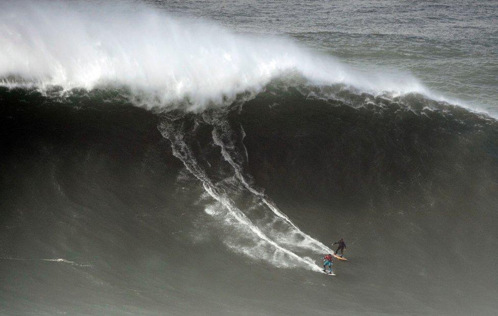 Dos surfistas cogen a la vez una ola durante el Tow Surfing Challenge en Nazaré.