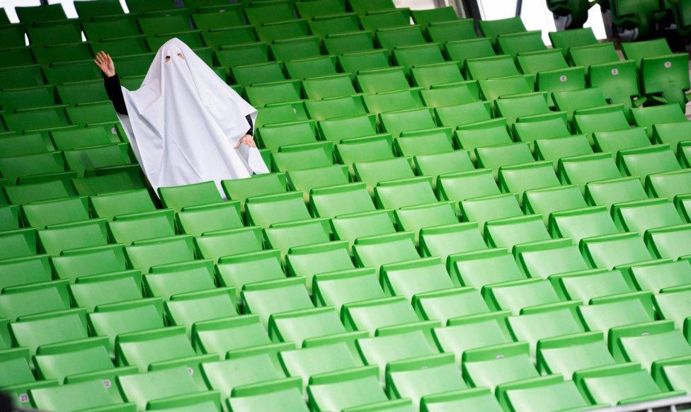Una persona disfrazada de fantasma posa en las gradas vacías antes del encuentro a puerta cerrada por la crisis del coronavirus de Europa League entre el Linzer ASK y el Manchester United en Linz, Austria.