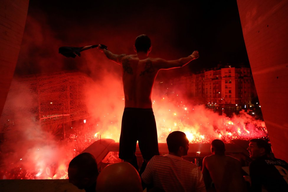 La imagen muestra al centrocampista argentino del Paris Saint-Germain, Angel Di María, y sus compañeros de equipo celebrando con los seguidores, que están reunidos fuera del estadio, la victoria en el partido de vuelta de los octavos de final de la Champions League entre el PSG y el Borussia Dortmund en París.