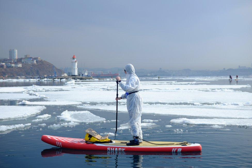 """Un surfista lleva un traje protector como muestra de apoyo a las personas que luchan contra la propagación de la enfermedad por coronavirus (COVID-19) participando en el evento anual de """"Hijacking an ice floe"""", que marca el comienzo de la temporada de surf de remo en pie, en Vladivostok, Rusia."""