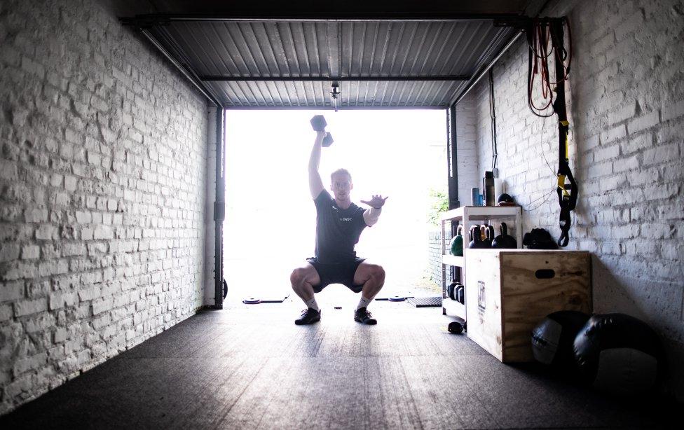 El entrenador personal Jan Terhorst hace una rutina de ejercicios en el garaje de su casa durante el confinamiento por el COVID-19.