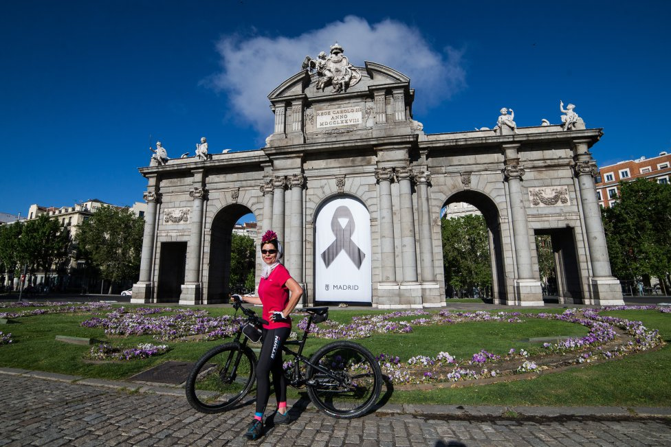 Una deportista con detalles del atuendo de chulapa en la Puerta de Alcalá, en la semana de San Isidro