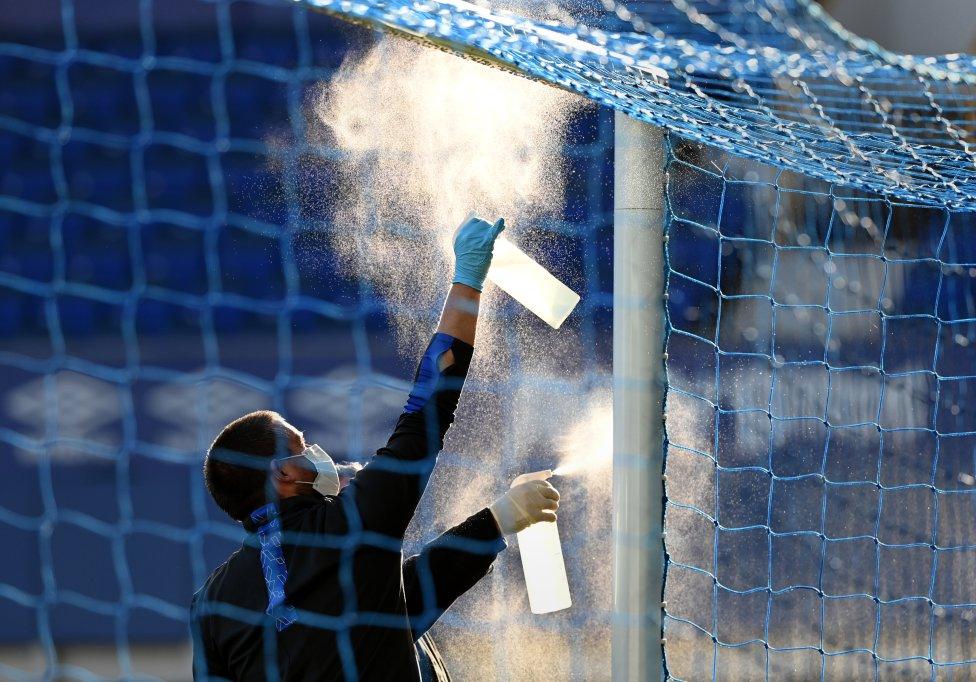 La red de la portería se rocía con desinfectante durante el partido de la Premier League entre el Everton FC y el Liverpool FC en Goodison Park en Liverpool, Inglaterra.