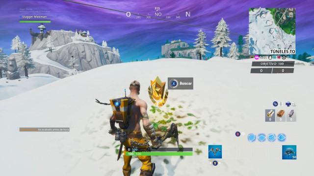 fortnite battle royale temporada 10 temporada x desafios taquillazo desafio busca entre una videocamara de sotano una cabeza de piedra nevada y un gran y llamativo trailer de oro