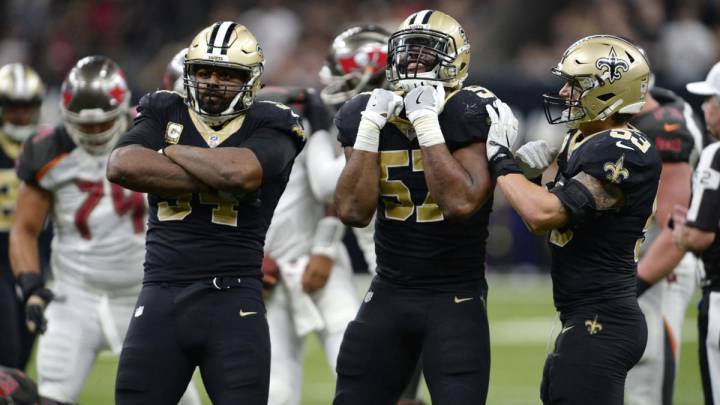 Defensivos de los Saints, incluyendo a Alex Okafor, posan y festejan