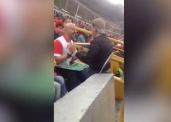 Caring father helps his blind son to follow a live football game